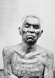 "Portrait of Chief Xana showing his chest and arm tattoos from W.H. Collison's ""In the Wake of the War Canoe"". Photographer uncredited."