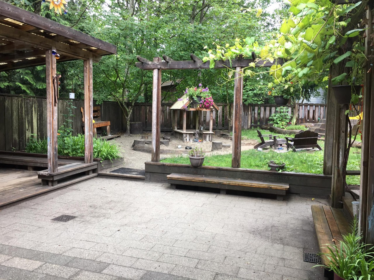 An outdoor play yard with grass and wooden structure
