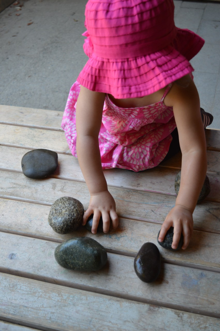 Child in pink hat and dress playing with rocks