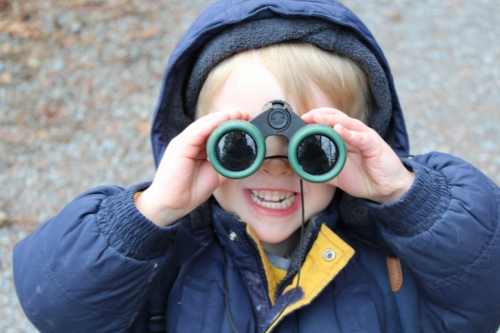 A child looking through binoculars