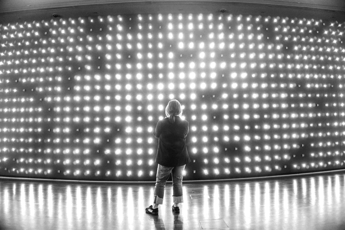 Black and white photo of women watching a light screen.