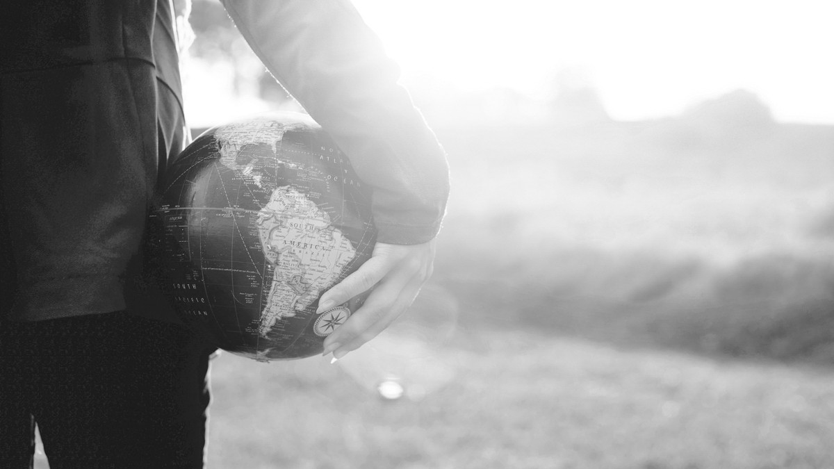 Black and white photo of hand holding world globe.