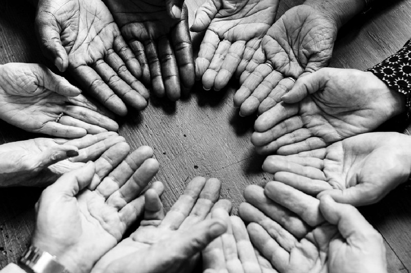 Black and white photo of hands coming together