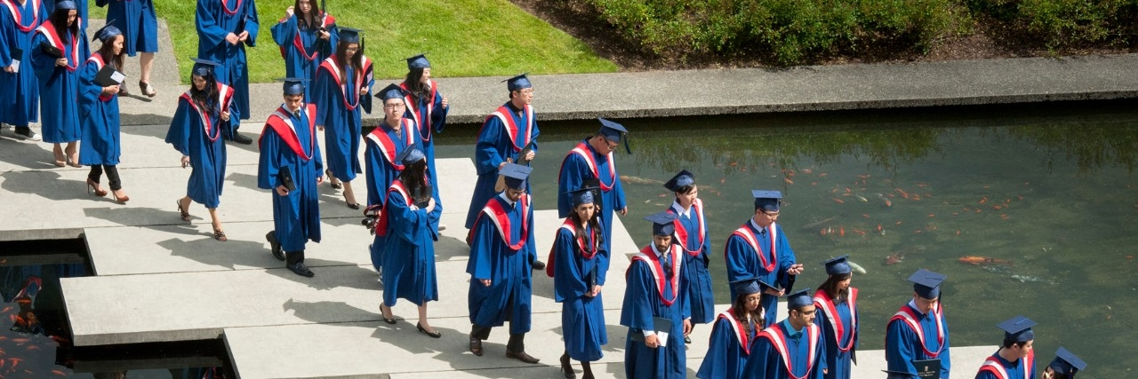 SFU graduates in regalia crossing the AQ pond on their way to the convocation ceremony