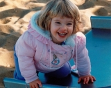 Photograph of Elise at 2 years old, crouched on a slide in a pink puffy parka and grinning at the camera.