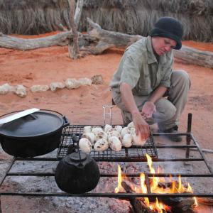 A +Khomani guide at //Uruke Bush Camp Adventures prepares bread buns on a grill