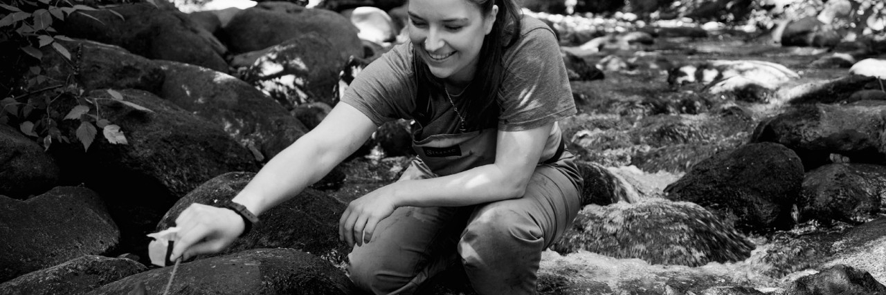 student in stream doing fieldwork