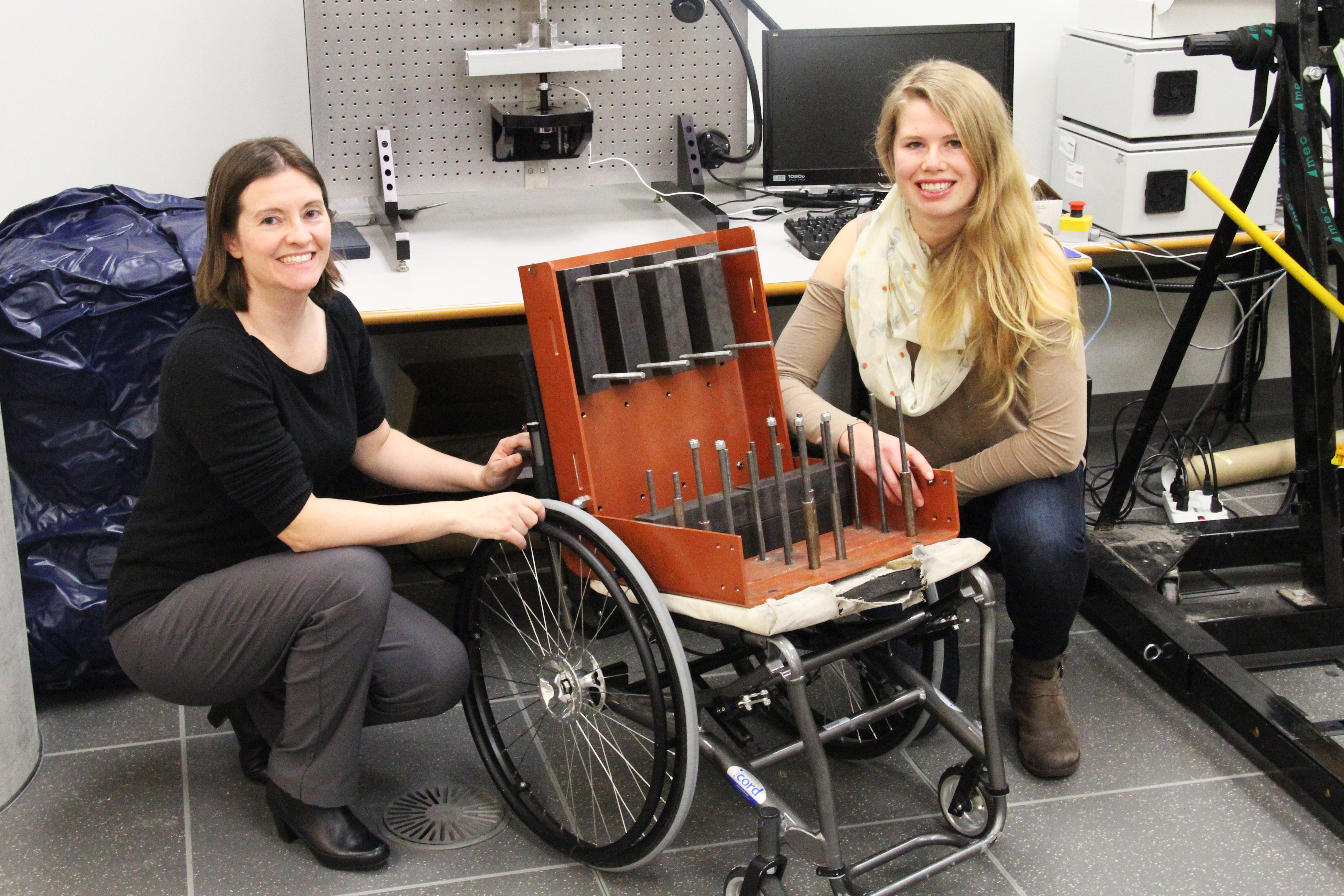 SFU mechatronics professor Carolyn Sparrey (left) and graduate student Louise Thomas (right) pose with the Elevation™ model manual wheelchair with test weights that mimic a seated person.