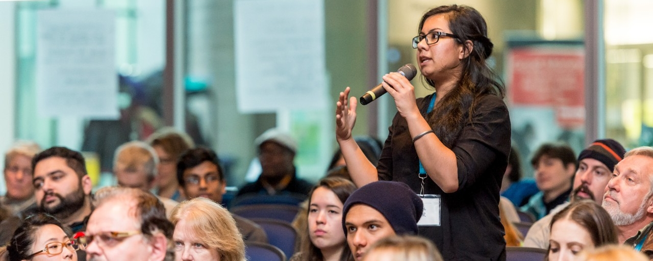 Woman standing speaking into microphone in audience