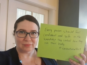 "Woman holding a paper sign that reads: """"Every person should feel confident and safe in the knowledge they control how they use their body. #consentmatters"""
