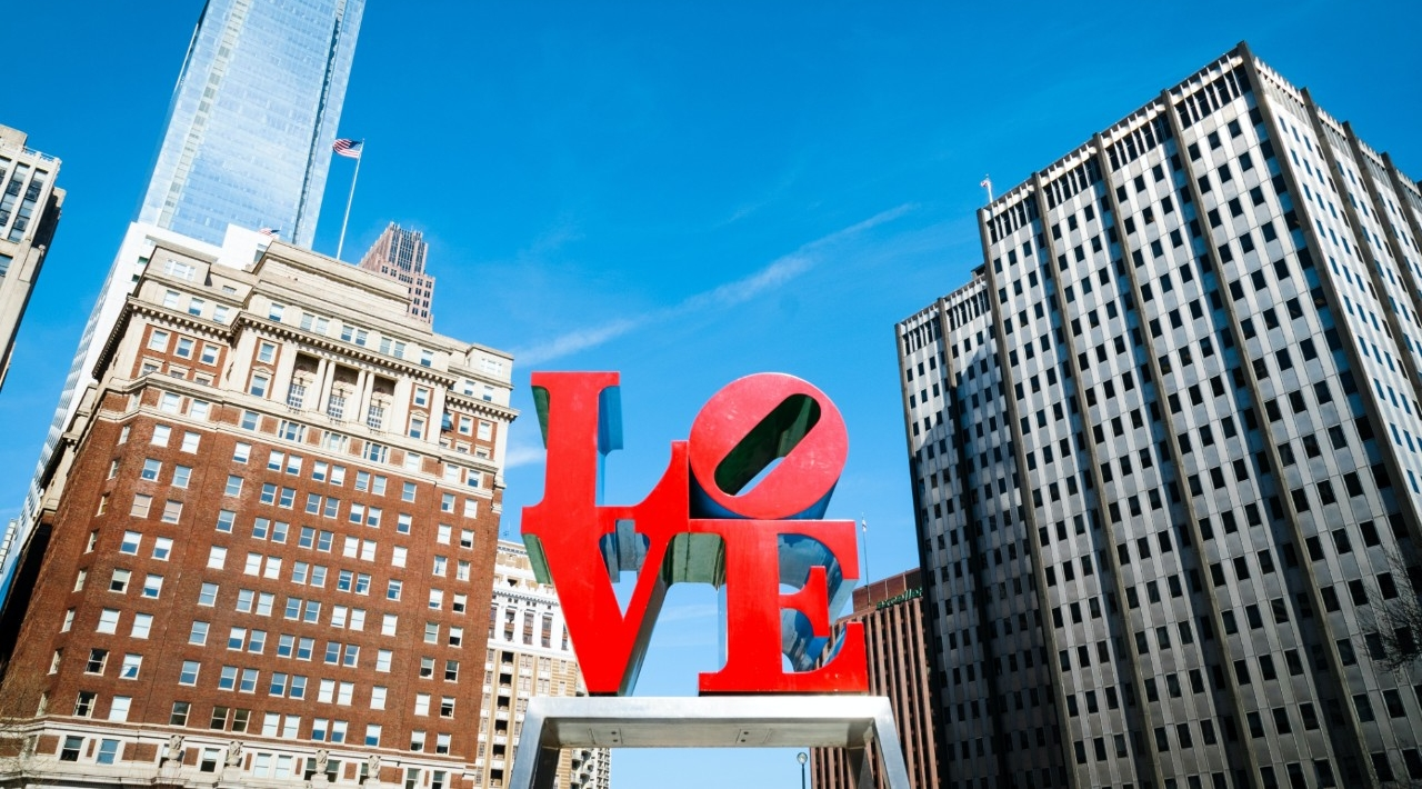 The letters L-O-V-E are silhouetted against a bright blue sky.