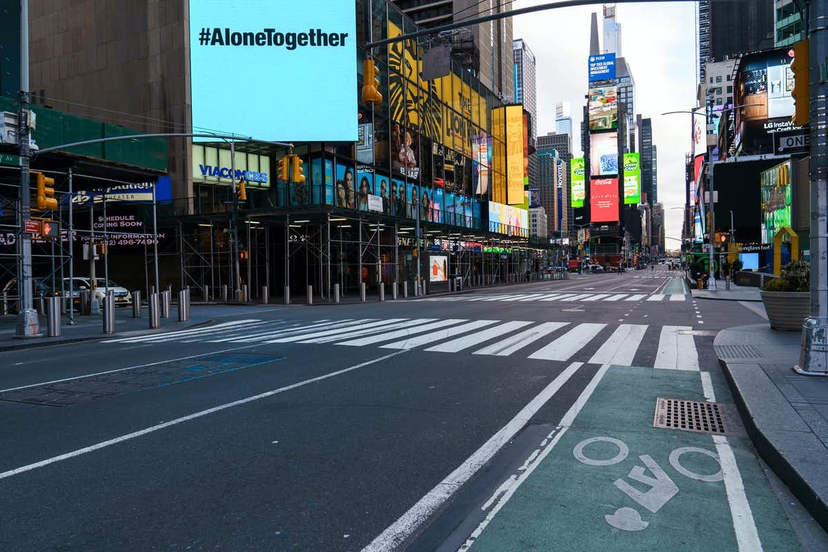 A billboard that says #AloneTogether shines above an empty New York City street.