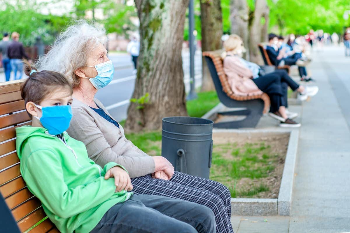 An older woman and a child sit on a park bench wearing masks.