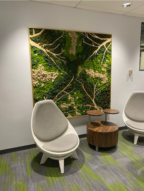 A grey chair sits in front of a wall with a mossy design in different shades of green.