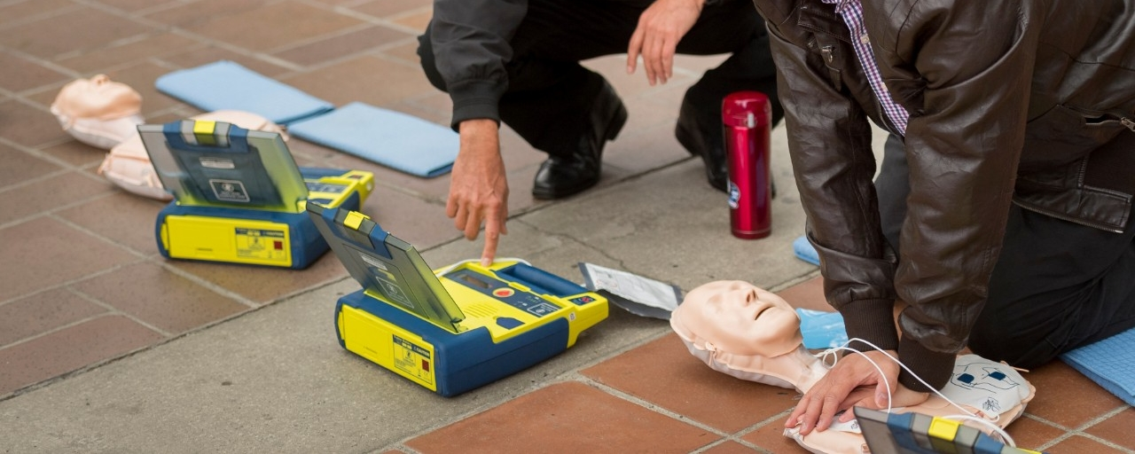 two individuals getting AED training