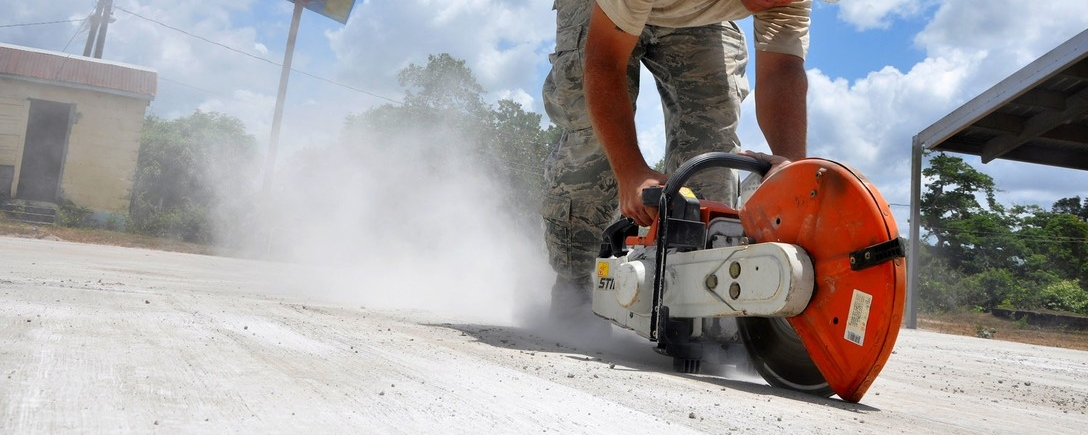man cutting concrete with saw