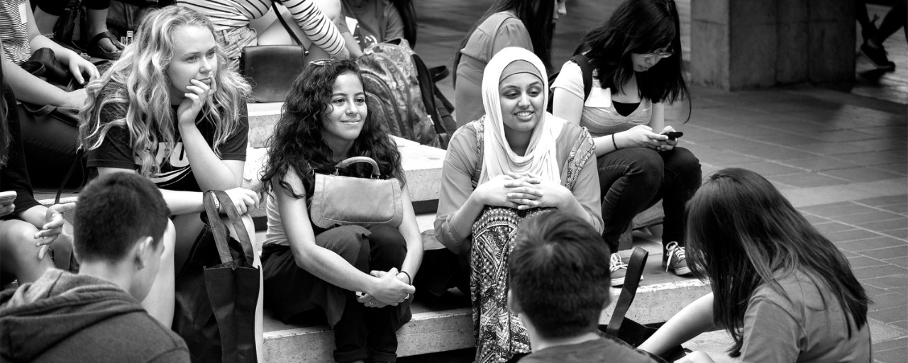 A female student smiling among a crowd.