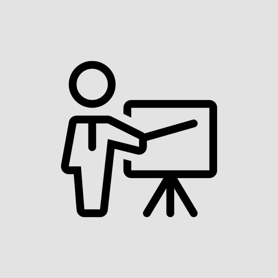 Black icon of a person pointing to a presentation board on a light grey background.