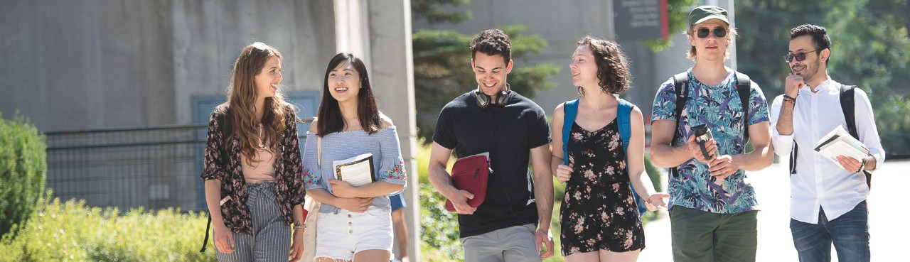 SFU residents walking outside residence towers while conversing and smiling.