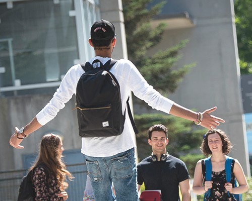 SFU resident greeting a group of his friends with open arms.
